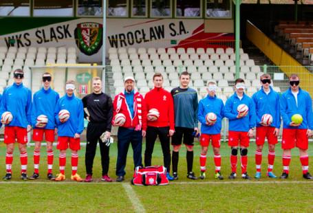 Zdjęcie przedstawia zawodników drużyny WKS Śląsk Wrocław stojących na murawie.