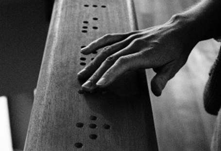 Na zdjęciu znajduje się dłoń czytająca słowo w języku Braille'a
