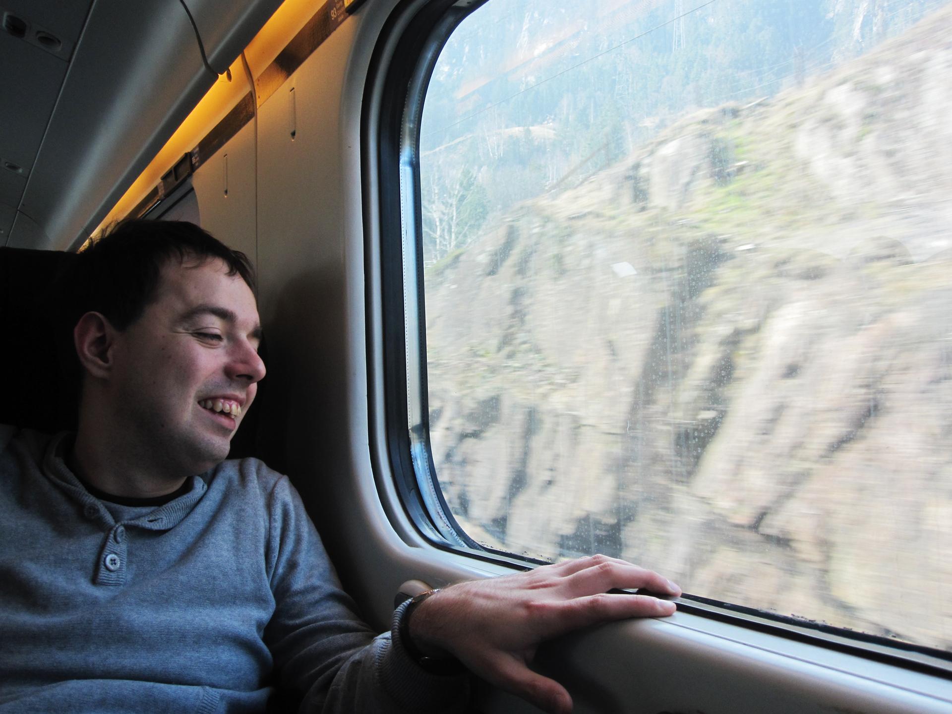 Portret autora bloga Filipa Zagończyka. Zdjęcie zrobione w pociągu, za oknami widać góry.