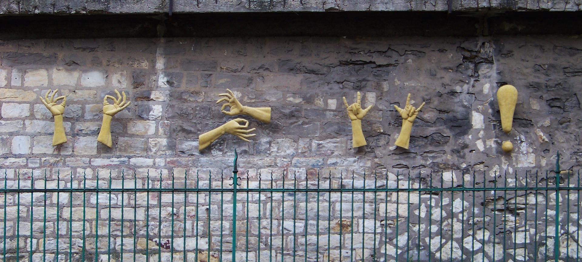 Rzeźba przedstawia dłonie, które gestami migowymi przedtawiają tytułową senstecję. Rzeźba znajduje się na murze szkoły dla niesłyszących w Pradze.