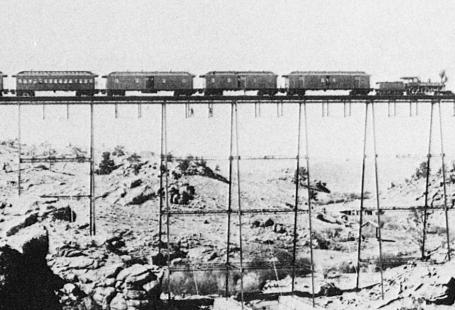 Fotografia przestawiająca most kolejowy oraz pociąg ok roku 1860.