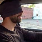Na zdjęciu mężczyzna z opaską na oczach kieruje samochodem. Materiały Towarzystwa Pomocy Głuchoniewidomym.