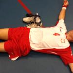 Zdjęcie przedstawia zawodnika polskiej drużyny leżącego na boisku na wznak, z rozłożonymi ręlami.