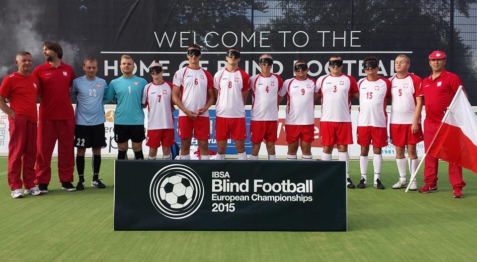 Zdjęcie przedstawia polską drużynę blind footbalową wraz z trenerami na płycie boiska.