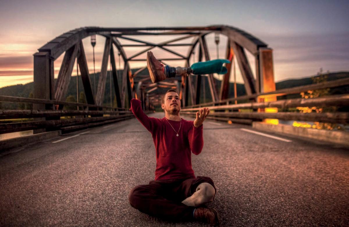 Zdjęcia przedstawia Jaśka Melę, który siedzi na drodzepo turecku i podrzuca do góry swoją protezę.
