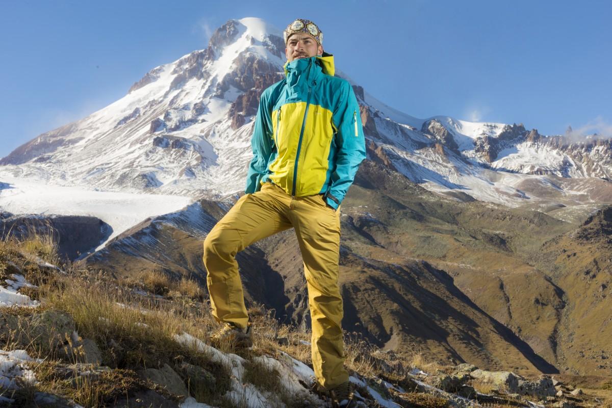 Zdjęcie przedstawia Janka Melę na tle górskiego, ośnieżonego szczytu.
