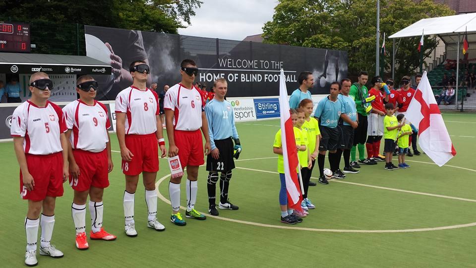 Zdjęcie przedstawia drużynę Polską oraz Angielską, przed rozpoczęciem meczu. Oprócz zawodników (po 5 w każdej drużynie) są również sędziowie oraz dzieci trzymające flagi narodowe.