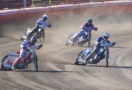 Zdjęcie przedstawia żużlowców jadących w biegu żużlowym. Czterej zawodnicy znajdują się na zakręcie stadionu.