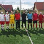 Na zdjęciu znajdują się zawodnicy polskiej drużyny blindfootballowej wraz z trenerami. Zawodnicy stoją na zielonej murawie boiska, stoją przodem, z rękami splecionymi z tyłu lub na baczność.