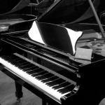 Zdjęcie przedstawia fortepian stojący w pomieszczeniu, przed nim znaduje się stołeczek, na którym ma siedzieć muzyk.