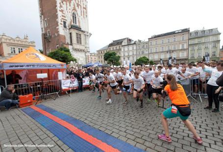 Zdjęcie przedstawia rozpoczęcie biegu na krakowskim Rynku. Z prawej strony plecami stoi kobieta z aparatem, robi zdjęcie startującym.