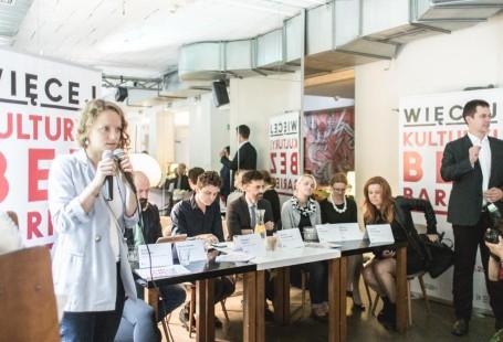 Zdjęcie przedstawia zarząd fundacji oraz przedstawicieli instytucji biorących udział w festiwalu. (Zachęta, Cenrum Nauki Kopernik,Terat Baj). Po lewej stronie stoi dziewczyna, prowadząca spotkanie za nią znajduje się stolik, przy którym siedzą wcześniej wymienieni.