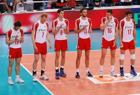 Zdjęcie przedstawia zawodników polskiej rezprezntacji piłki siatkowej w 2010. Stoją w rzędzie na boisku przed meczem, 14 zawodników. Przed nimi widać dzieci niosące polską flagę.