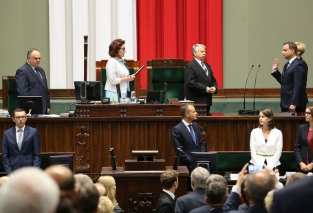 Zdjęcie przedstawia prezydenta Andrzeja Dudę składającego przysięgę przed Zgromadzeniem Narodowym. Na zdjęciu znajduje się z prawej strony, ma prawą rękę uniesioną do góry. Zdjęcie jest wykonane w Sejmie, w centrum fotografi znajduje się marszałkini Małgorzata Kidawa-Błońska, która jest zwrócona do prezydenta i czyta treść przysięgi. W tle widać polską flagę.