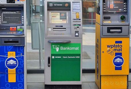 Zdjęcie przedstawia pięć bankomatów stojących w rzędzie obok siebie.