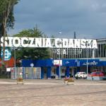 Zdjęcie przedstawia historyczną Bramę nr 2 Stoczni Gdańskiej. Nad bramą widnieje duży napis Stocznia Gdańska S.A. obok duże drzewa, obok znajduje się prostopadłościenny pominik z kamienia, na płocie wisi baner Solidarność.