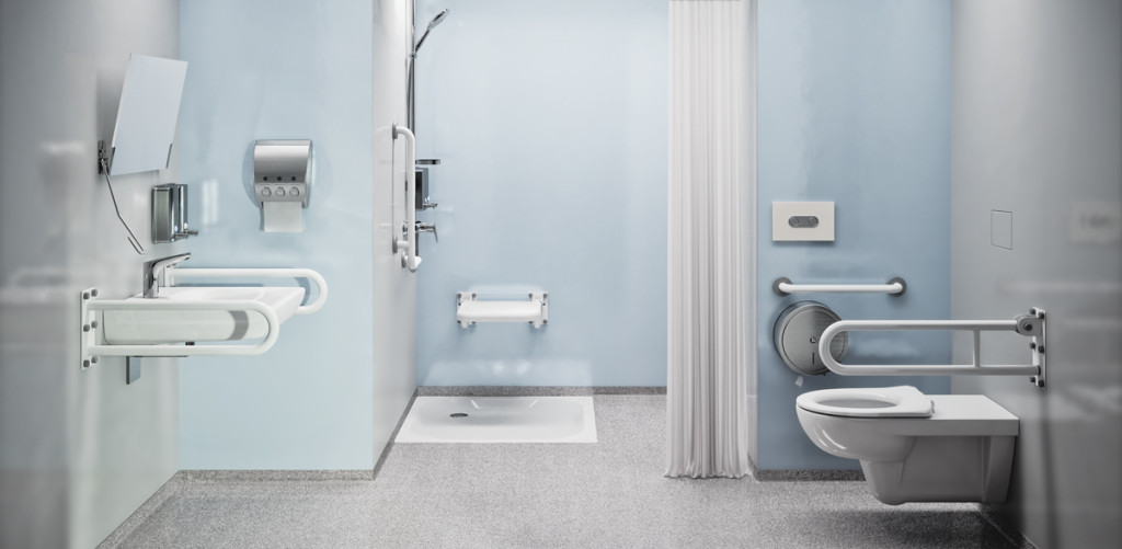 Zdjęcie przedstawia wnętrze łazienki. Po prawej stronie znajduje się toaleta ze wspornikami umowowanymi w ścianach, po lewej umywalka również ze wspornikami oraz lustro. W tle znajduje się kabina prysznicowa z ze wspornikiem oraz krzesełkiem.