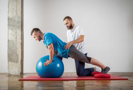 Zdjęcie przestawia fizjoterapeutę oraz pacjenta. Pacjent opiera się rękami na gumowej kuli do ćwiczeń, stopy ma oparte na macie do ćwiczeń. Fizjoterapeuta klęczy za nim i ma ręce położone na jego biodrach.