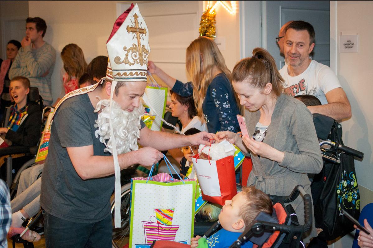 Zdjęcie przedstawia Mikołajki w klinice Budzik na pierwszym planie znajduje się Mikołaj, którym jest Czesław Śpiewa - wręcza dziecku, które jest na wóżku prezent. Obok stoi mama chorego.