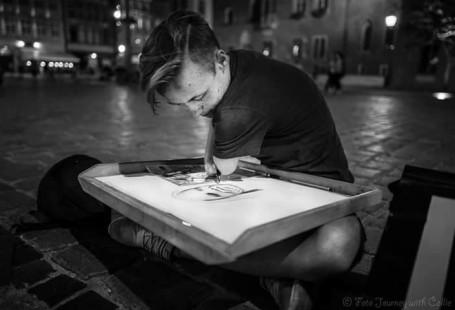 Zdjęcie przedstawia Mateusza Kędzierskiego, który rysuje, w tle widać miasto.