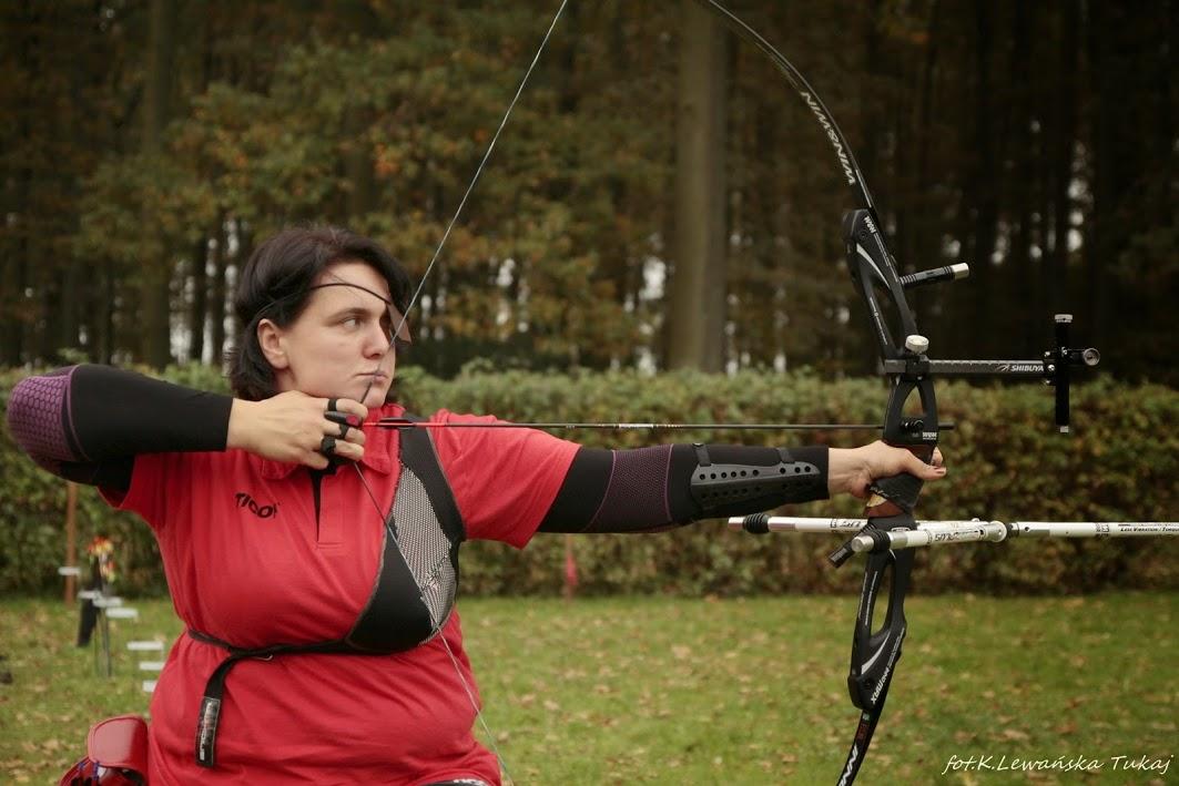 Zdjęcie przedstawia Milenę Olszewska podczas turnieju łuczniczego. Stoi bokiem, jest w momencie naciągnania strzały. Na jednym oku ma opaskę.