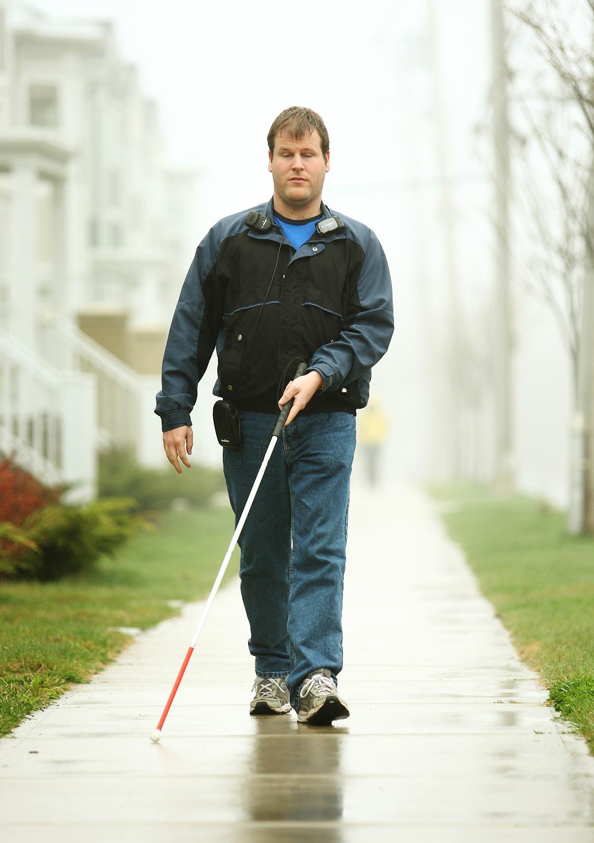 Zdjęcie przedstawia mężczyznę, najprawdopodobniej niewidomego, idacego chodnikiem przez osiedle. Przed sobą trzyma białą laske z czerwonym zakończeniem. Ubrany jest na sportowo.