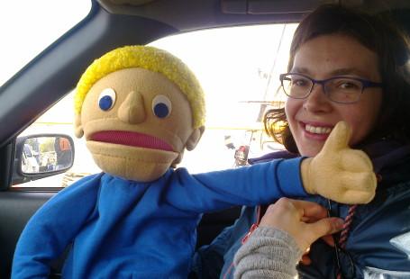 Zdjęcie przedstawia lalkę Franka siedzącego razem z kobietą z fundacji w samochodzie. Kobieta trzyma lalkę na kolanach, na swojej dłoni podpiera dłoń lalki, która ma wyciągnięty do góry kciuk.