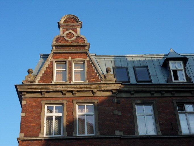 Zdjęcie 40x60, widok poziomy. Przestrzeń zdjęcia wypełnia fragment starej kamienicy z czerwonej cegły na tle błękitnego nieba. Widoczne jest ostatnie piętro i blaszany dach budynku, zakończony z jednej strony wieżyczką. Wieżyczka też jest z czerwonej cegły, a w jej trójkątnym froncie znajdują się dwa jednoskrzydłowe okna. Po ich obu stronach betonowe ozdobniki w kształcie uchwytu dawnej pieczątki. Nad oknami dekoracyjne, smukłe wykończenie wieżyczki. Obok wieżyczki, z prawej strony, znajdują dwa okna dachowe, trzecie jest w ozdobnym erklu zwieńczonym spiczastym blaszanym daszkiem. Na widocznym piętrze są cztery dwuskrzydłowe okna w białych ramach. Murowana, brązowa obwódka wyraźnie oddziela okna od elewacji. Piętro i dach są rozdzielone ozdobnym gzymsem w kolorze brązowym.