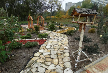 Zdjęcie przedstawia fragment ogrodu. Na środku znajduje się ścieżka z położonych dosyć dużych kamieni o nieregularnych kształtach. Na pierwszym planie, obok ścieżki znajduje się karmnik dla ptaków wykonany z gałęzi brzozy, W tle znajduje się mostek, do którego wiedzie ścieżka, kwiaty i krzewy w różnych kolorach i wielkościach oraz drzewa. W oddali widać szare, wysokie bloki.