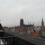 Zdjęcie 40 x 60, w układzie poziomym. Z tarasu Teatru Szekspirowskiego, na tle szarego nieba, widać budynki Starego Miasta. Wśród nich dwie charakterystyczne budowle: po prawej stronie średniowieczny Ratusz Głównego Miasta a pośrodku Bazylikę Mariacką. Ratusz to strzelista, ostro zakończona wieża z ozdobnymi kolumnami i kopułami, na widocznych ścianach ogromne tarcze zegarowe. Natomiast bazylika ma potężne mury i wieże, w tym górująca nad całością kwadratowa wieża główna, zakończona czerwonym dachem. Resztę zdjęcia wypełniają kilkukondygnacyjne stare kamieniczki z czerwonymi dachami oraz szarymi i brązowymi elewacjami. Przód zdjęcia to balustrada tarasu widokowego.