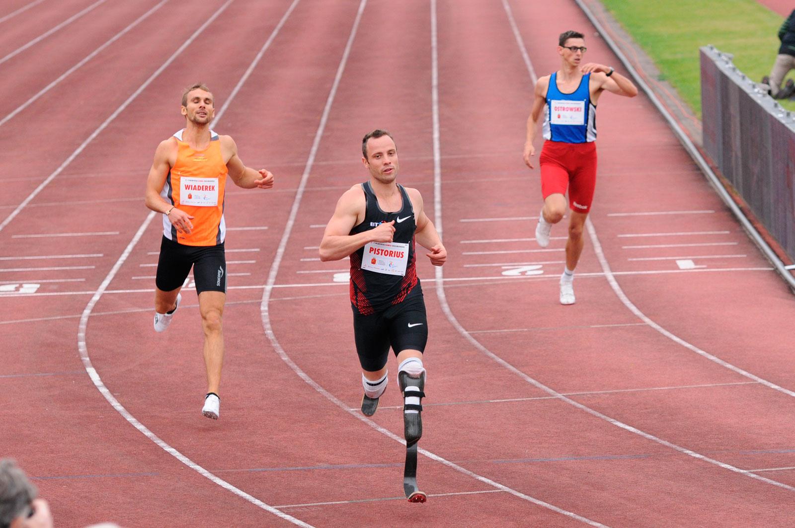 Zdjęcie przedstawia Oskara Pistoriusa na stadionie, na bieżni. Za nim znajduje się dwóch zawodników, po lewej i prawej stronie.