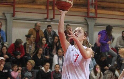 Zdjęcie przedstawia Natasę w czasie rzutu do kosza. Widoczna jest do pasa, ma prawą rękę wyciągniętą do góry w niej trzyma piłkę. W tle widać trybuny i widownię.