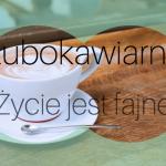 Zdjęcie przedstawia filiżankę kawy z łyżeczką na drewnianym stole.