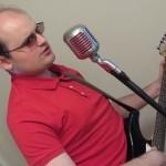Zdjęcie przedstawia Adama WIśniewskiego śpiewającego do mikrofonu i grającego na gitarze.