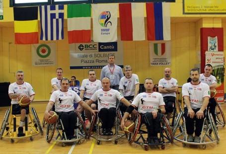 Na zdjęciu widać zawodników drużyny, siedzących na wózkach w dwóch rzędach - w pierwszym siedzą 4 osoby, w kolejnym 6, za nimi stoi trener. Zdjęcie jest zrobione na sali gimnastycznej, pod sufitem wiszą flagi, na ścianie plakaty.