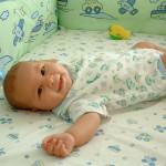 Zdjęcie przedstawia niemolę leżące w łóżeczku, uśmiechające się.