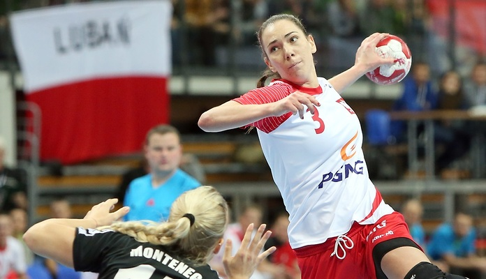 Zdjęcie przedstawia Monikę Kobylińską w czasie rzutu na bramkę. Zawoniczka wyskakuje ponad obronę, w prawej ręce trzyma piłkę i zaraz odda rzut na bramkę.