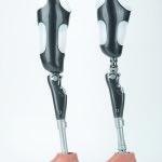 Zdjęcie przedstawia dwie protezy nóg firmy Mark Protetik, wykonane z włókna węglowego.