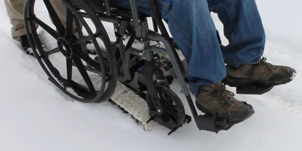 Zdjęcie przedstawia wózek umieszczony na gąsienicach freedom trax. Wózek stoi na śniegu i widać jednyni nogi o osoby siedzącej.