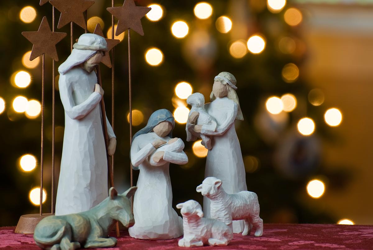 Zdjęcie przedstawia szopkę bożonarodzeniową, w której figurki świętej rodziny oraz baranków są wyrzeźbione z drewna.
