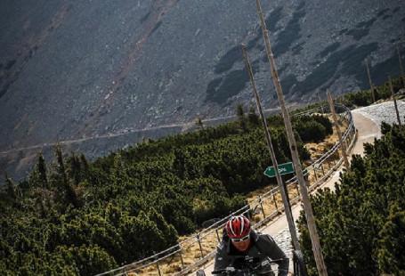 Zdjęcie przedstawia mężczyznę zjeżdżającego drogą ze szczytu na handbike'u. Szczyt góry widnieje w tle za nim, góra jest wysoka.
