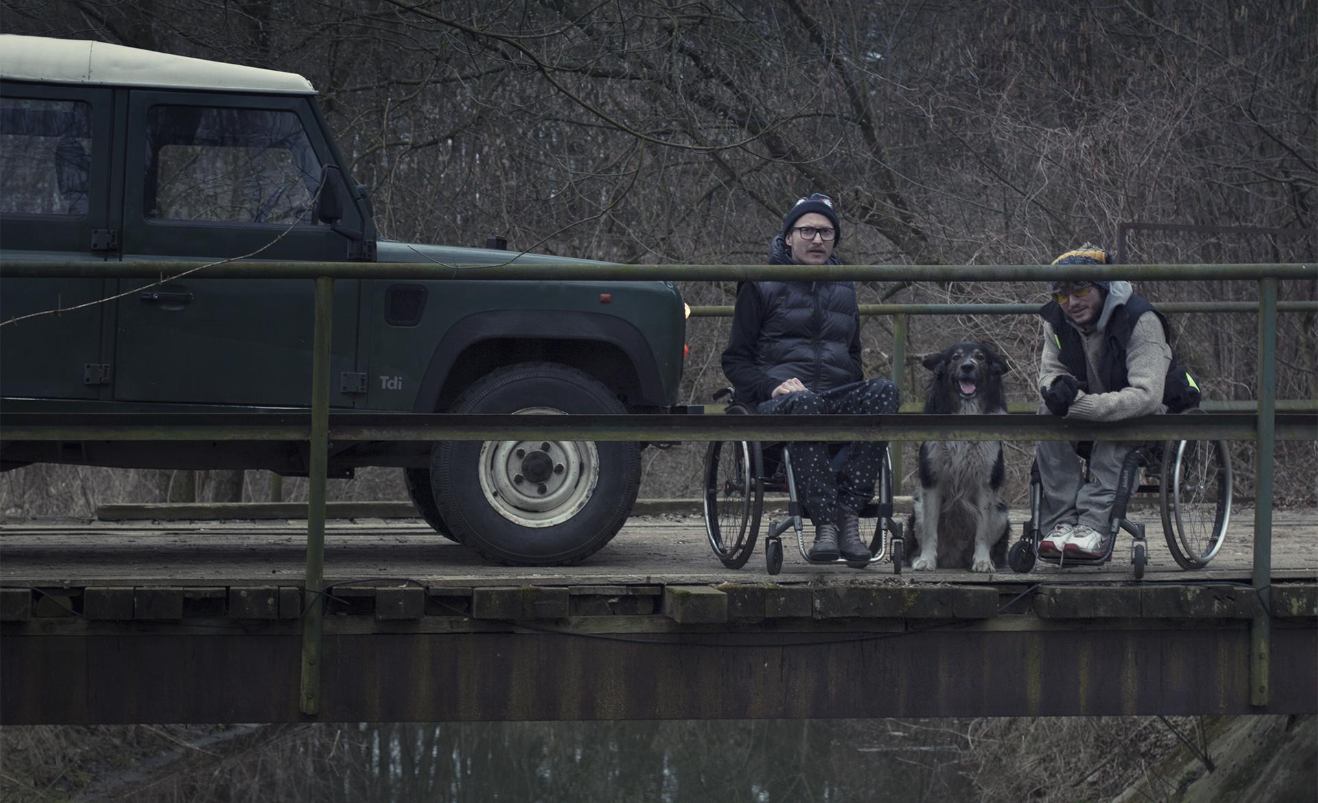 Zdjęcie przedstawia Michała Worocha oraz Marcina Kamińskiego siedząych na wózkach. Między nimi znajduje się pies, obok stoi samód terenowy.