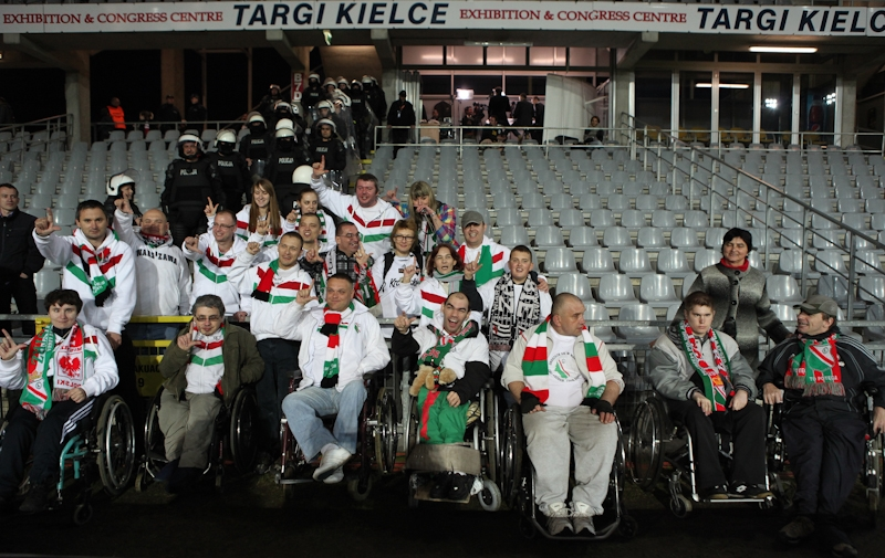 Zdjęcie przedstawia niepełnosprawnych kibiców legii na stadionie przed meczem w hali w Kielcach.