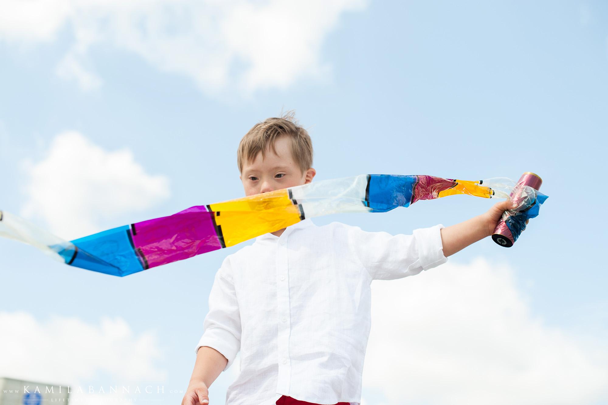 Na zdjęciu widzony jest Maks, ubrany w białą koszulę, bawi się kolorowym szalikiem, który powiewa na wietrze.