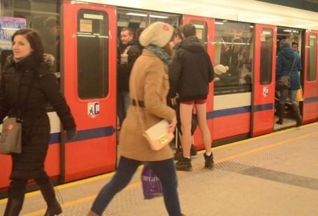 Zdjęcie przedstawia chłopaka, który wsiada do metra ubrany w kurtkę oraz bokserki.