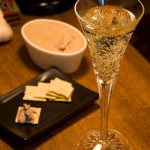 Zdjęcie przedstawia kieliszek szampana stojący na stole.