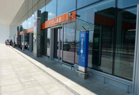 Zdjęcie przedstawia omówiony w atykule pylon SOS, jest to prostokątny słup, na którym znajduje się guzik z napisem SOS, stojący obok wejścia na lotnisko.