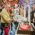 Zdjęcie przedstawia Jerzego Owsiaka, który zaraz zacznie kroić tort, na którym jest serce wielkiej orkiestry oraz są wbite zimne ognie.