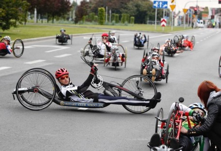 Zdjęcie przedstawia Rafała Wikla na handbike'u przed startem, w okól znajdują sie inni zawodnicy.