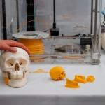 Zdjęcie przedstawia czaszkę wraz z implantem wydrukowaną tehnice druku 3D. Widać czaszkę ze wstawionym innego koloru bio-implantem w szczęce, z tyłu znajduje się drukarka 3D.